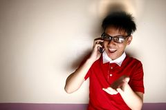 Teenage kid talking on a smartphone and smiling Stock Photography