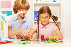 Teenage kids creating wind generator turbine model. Two teenage kids, boy and girl, creating working wind generator turbine model at the physics lesson Royalty Free Stock Image