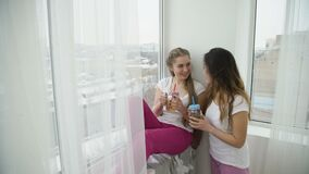 Teenage leisure communication friendship drinks. Carefree teenage leisure. communication friendship. bored young girl sitting on the windowsill and looking out stock video