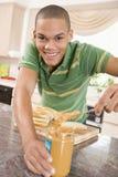 Teenage Male Making Peanut Butter Sandwich stock images
