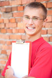 Teenage male student with blank clipboard Royalty Free Stock Image