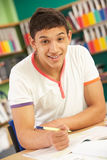Teenage Male Student In Classroom. Teenage Male Student Working In Classroom Royalty Free Stock Image