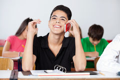 Teenage Male Student Using Phone In Classroom. Happy teenage male student using phone while sitting at desk in classroom Stock Image