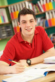 Teenage Male Student In Working In Classroom. Looking at camera Stock Images