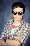 Teenage male in sunglasses. Half body portrait of handsome male teenager with sunglasses and check shirt; studio background Stock Photography