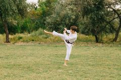 Karate boy in action. Judo training on a park background. Fighting concept. Copy space. Teenage male in a traditional kimono training on a park background royalty free stock photos
