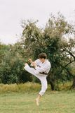 Karate boy in action. Judo training on a park background. Fighting concept. Copy space. Teenage male in a traditional kimono training on a park background stock images