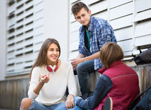 Teenage males and girl talking. Portrait of teenage males and girl talking in autumn day outdoor royalty free stock photo