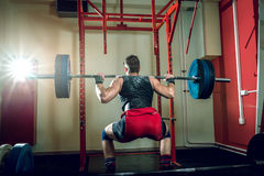 Teenage man doing squats indoor. royalty free stock images