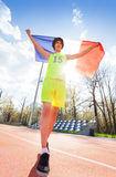 Teenage marathon winner with flag of France behind. Full-length portrait of teenage boy in sportswear, running with flag of France outside on the track Stock Photos
