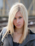 Teenage Model in Gray Jacket. An image of a pretty blonde teenager looking at the viewer in an outdoor setting Stock Photography