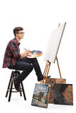 Teenage painter with paintbrush and palette looking at canvas royalty free stock photo