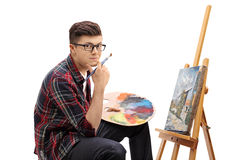 Teenage painter with a paintbrush and a palette. Sitting in front of a canvas and looking at the camera isolated on white background royalty free stock photography