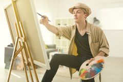 Teenage painter painting with a brush on a canvas. Indoors stock photography