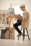 Teenage painter painting on a canvas Royalty Free Stock Image