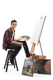 Teenage painter sitting in front of a blank canvas royalty free stock photography
