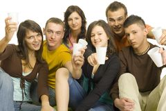 Teenage party. Group of 6 teenagers sitting together. They're holding plastic cups and look like have party. White background Stock Photos