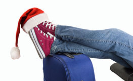 Teenage passenger with santa hat. Young boy with his legs over the suitcase waiting on white background with santa hat on the feet Royalty Free Stock Photo