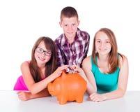 Teenage putting coins into big piggy bank Royalty Free Stock Photos