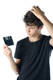 Teenage puzzled with floppy disk in his hand Stock Images