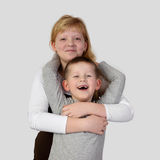 Teenage redhead girl embraces little toothless smiling boy. Teenage blonde girl embraces little toothless smiling boy on gray background in square - Elder sister Royalty Free Stock Images