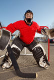 Teenage road hockey goalie outside on street Stock Photos