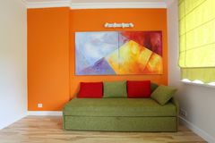 Teenage room. Orange wall and green sofa in teenage room Royalty Free Stock Photos