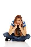 Teenage sad woman sitting on the floor.  Royalty Free Stock Photo