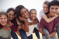 Teenage school friends having fun piggybacking outdoors Royalty Free Stock Photos