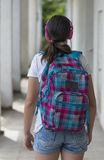 Teenage school girl with a backpack on her back and headphones Stock Images