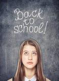 Teenage school girl looking up on the chalkboard background Stock Photography