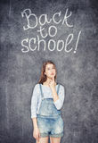 Teenage school girl looking up on the chalkboard background. Young teenage school girl looking up on the chalkboard background Royalty Free Stock Photos