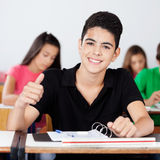 Teenage Schoolboy Gesturing Thumbs Up In Classroom. Portrait of happy teenage schoolboy gesturing thumbs up while sitting at desk in classroom Royalty Free Stock Photo