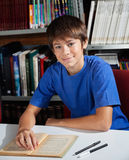 Teenage Schoolboy Smiling While Sitting In Library Stock Images