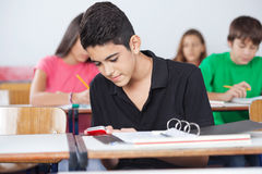 Teenage Schoolboy Text Messaging At Desk. Teenage schoolboy text messaging on cellphone while sitting at desk in classroom Royalty Free Stock Photos