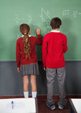 Teenage Schoolchildren Writing On Board Stock Photography
