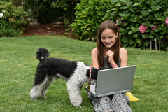 Teenage schoolgirl with dog  and notebook. Teenage girl  with laptop.Teenager with wonderful long brown hair sitting on the grass and shoes her dog how to work Royalty Free Stock Images