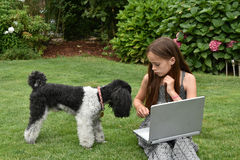 Teenage schoolgirl with dog  and notebook. Teenage girl  with laptop.Teenager with wonderful long brown hair sitting on the grass and shoes her dog how to work Stock Image