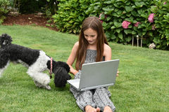 Teenage schoolgirl with dog  and notebook. Teenage girl  with laptop.Teenager with wonderful long brown hair sitting on the grass and shoes her dog how to work Stock Photo