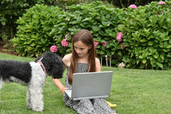 Teenage schoolgirl with dog  and notebook. Teenage girl  with laptop.Teenager with wonderful long brown hair sitting on the grass and shoes her dog how to work Royalty Free Stock Image