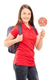 Teenage schoolgirl holding a colorful lollipop Stock Photos