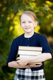 Teenage schoolgirl holding pile of books and smiling. Adorable happy blond schooler girl ready back to school, holding pile of textbooks, school books, manuals stock image