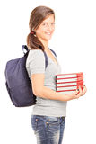 Teenage schoolgirl holding a stack of books Stock Photography