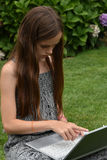 Teenage schoolgirl with notebook. Teenage girl with laptop.Teenager with wonderful long brown hair sitting on the grass working with notebook. back to school royalty free stock images