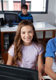 Teenage Schoolgirl Sitting In Computer Lab. Portrait of teenage schoolgirl sitting at desk with classmates in computer lab Royalty Free Stock Photos