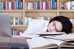 Teenage schoolgirl sleeping in library Stock Images