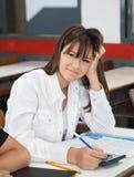 Teenage Schoolgirl Using Calculator At Desk. Portrait of teenage schoolgirl using calculator at desk in classroom Stock Photography