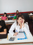 Teenage Schoolgirl Using Cellphone While Writing Royalty Free Stock Image