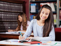 Teenage Schoolgirl Writing In Book At Table Stock Photo