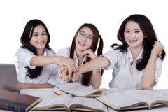 Teenage schoolgirls joining hands Stock Photos